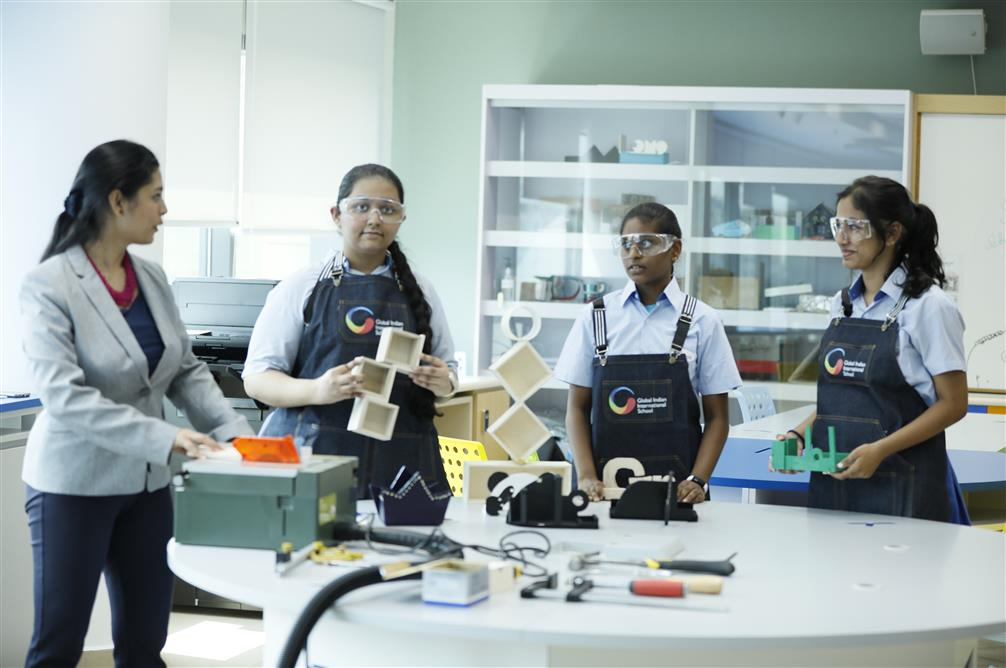 Teacher giving hands-on experience to GIIS student at the Design Studio in GIIS SMART Campus